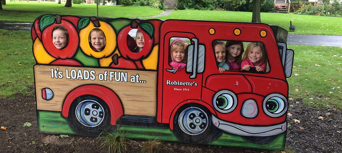 2016-2017 Second grade class faces through a wooden truck at Robinette's
