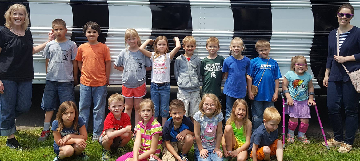 2016-2017 First Grade Class in front of a bus